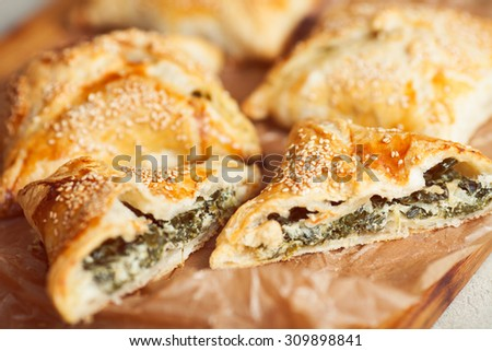 Vegetarian food concept. Baked chaussons with seeds of sesame filled with spinach and soft feta cheese inside,  on wooden board with parchment paper in cafe. French cuisine. Close up. Indoor shot - stock photo