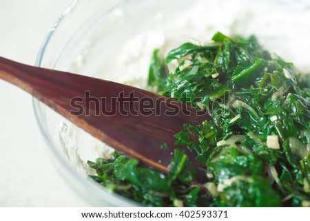Vegetarian food concept. Cooked sauteed spinach with garlic and onion in glass bowl. Close up. Indoor shot