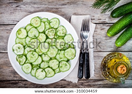 Vegetarian green salad with fresh organic cucumbers and dill with olive oil - stock photo