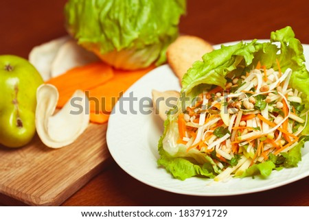 Vegetarian kitchen & healthy food concept. Fresh vegetable salad of celeriac, carrot, apple, iceberg lettuce and pignolia (pine) nut. Ingredients on wooden cutting board. - stock photo