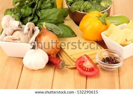 Vegetarian lasagna ingredients on wooden background - stock photo