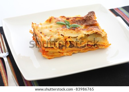 Vegetarian lasagna with eggplant, courgette, sweet potatoes and tomato sauce on a white plate. - stock photo