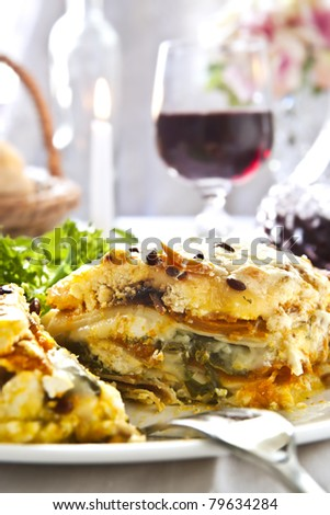 Vegetarian lasagne with a glass of red wine. - stock photo