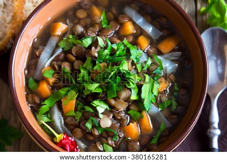 Vegetarian lentil soup (stew) with vegetables and parsley on rustic wooden background - stock photo