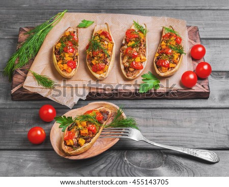 Vegetarian lunch Baked stuffed white eggplant stuffed with Baked and fresh vegetables, pumpkin, cherry tomatoes, chopped eggplant pulp, dill, parsley on gray background wooden surface, board - stock photo