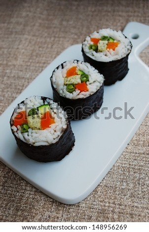 Vegetarian maki sushi rolls with rice, carrots, zucchini, green beans, tofu and nori seaweed in white dish on natural background - stock photo