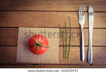 Vegetarian Meal - A ripe red tomato on a place mat with chives and cutlery on a wooden table top - stock photo