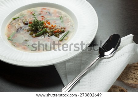 Vegetarian minestrone soup on a wooden table with a spoon and bread. Italian cuisine. - stock photo