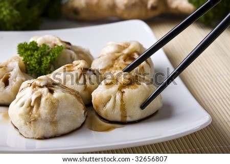 Vegetarian, oriental dumplings with soy sauce. Focus on dumpling being picked by the chopsticks. - stock photo