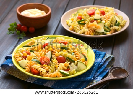 Vegetarian pasta salad of tricolor fusilli, sweet corn, cucumber and cherry tomato with mayonnaise in the back, photographed with natural light (Selective Focus, Focus one third into the first salad)  - stock photo