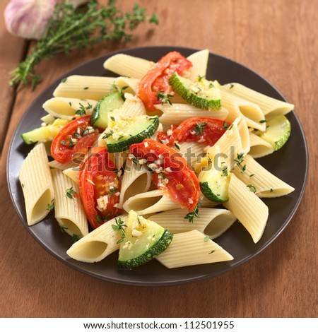 Vegetarian penne pasta dish with baked zucchini and tomato spiced with thyme and garlic (Selective Focus, Focus on the tomato slices in the lower part of the dish) - stock photo