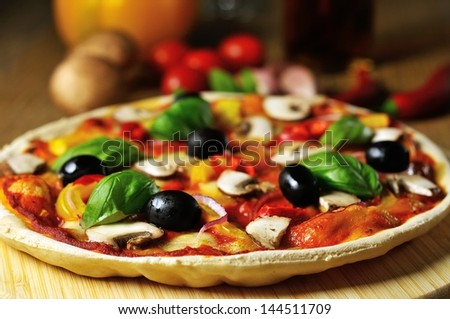 vegetarian pizza on wooden board with ingredients from the side - stock photo
