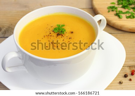 Vegetarian pumpkin soup in white bowl on wooden table with fresh green herbs - stock photo