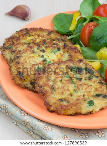 Vegetarian quinoa pancakes with salad from spinach, cherry tomatoes and bell pepper - stock photo