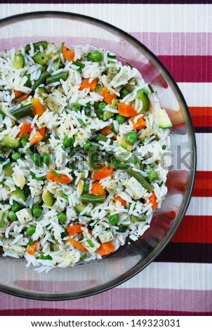 Vegetarian salad of white basmati rice with carrots, zucchini, green beans, peas, tofu and chives in a glass bowl on colorful background - stock photo