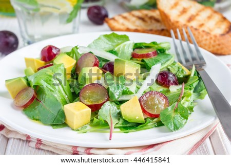 Vegetarian salad with avocado, grape, rucola, onion with vinegar dressing, on white plate, horizontal - stock photo