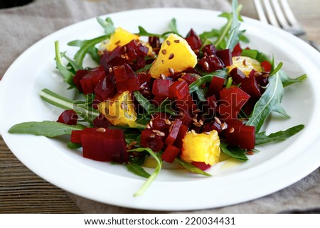Vegetarian salad with beet and orange on a plate, food closeup - stock photo