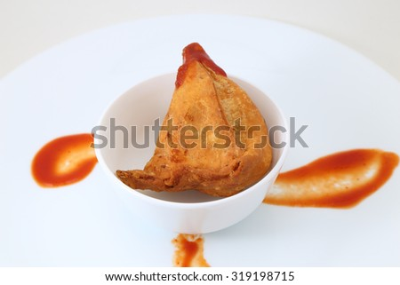 Vegetarian Samosa with sauce in a white ceramic plate. Indian traditional food. - stock photo