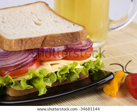 Vegetarian sandwich close up, with cheese, lettuce, tomato and onion in white bread. A glass of clod beer on the background.