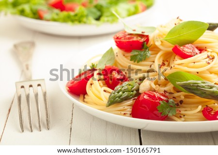 Vegetarian spaghetti pasta with fresh green asparagus spears, tomato and herbs served with a leafy green salad - stock photo