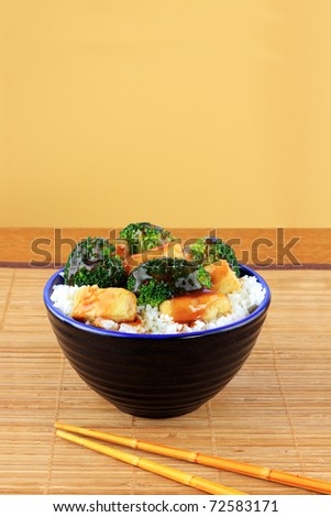Vegetarian Stir Fry dish of crispy tofu, broccoli and orange sauce with chopsticks. - stock photo