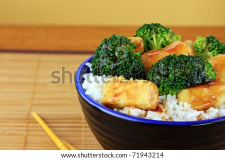 Vegetarian Stir Fry dish of crispy tofu, broccoli and orange sauce with chopsticks. Shallow DOF. - stock photo