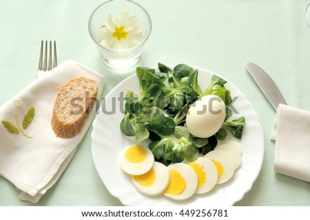 vegetarian summer lunch, a fresh salad with boiled egg and a slice of whole wheat bread