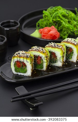 Vegetarian sushi roll with avocado ginger wasabi and chuka salad over black background - stock photo