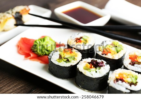 Vegetarian sushi rolls on plate, on wooden background - stock photo