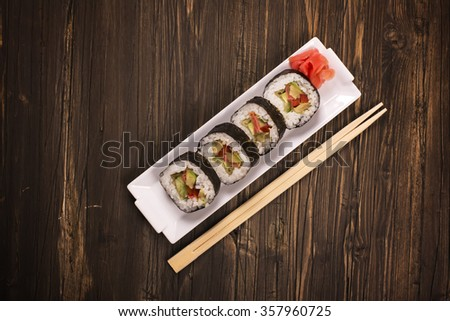 Vegetarian sushi rolls with chopsticks over brown wooden background. Top view. Toned image. Selective focus - stock photo