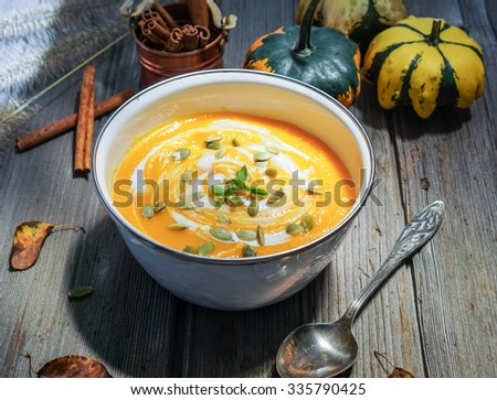 Vegetarian tasty spicy pumpkin soup bowl on a wooden background/ Selective focus - stock photo
