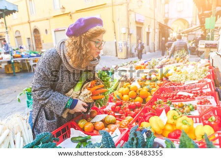 Vegetarian vegan young woman buying vegetables at local market. She is looking at some tomatoes, holding carrots on her harms. Sustainable cultivation concept. - stock photo