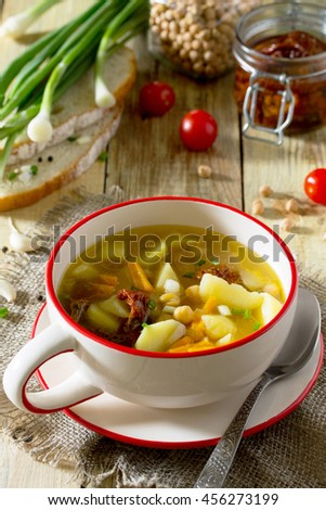 Vegetarian vegetable soup with chickpeas, potatoes and dried tomatoes on a rustic background, healthy eating, diet, vegetarian cuisine and the concept of cooking. - stock photo