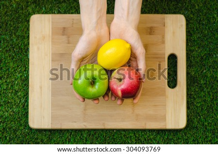 Vegetarians and cooking on the nature of the theme: human hand holding a red, apple green and lemon yellow on the background of a cutting board and green grass top view - stock photo