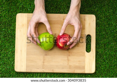 Vegetarians and cooking on the nature of the theme: human hand holding red and green apples on the background of a cutting board and green grass top view - stock photo
