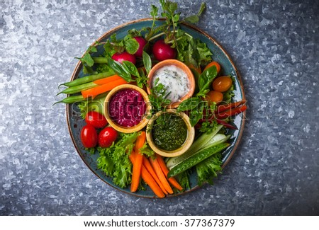 Veggie crudite platter with three different dips on the metal background - stock photo