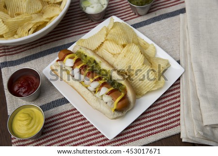 Veggie hot dog topped with mustard, ketchup, onions and relish, served with potato crisps (chips).