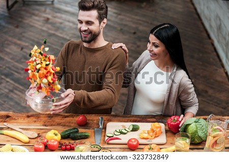 Veggie magic. Top view of beautiful young smiling couple preparing food together  - stock photo