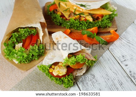 Veggie wrap filled with chicken and fresh vegetables on wooden table, close up