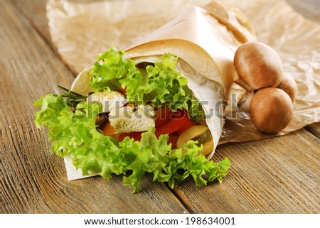 Veggie wrap filled with chicken and fresh vegetables on wooden table, close up - stock photo