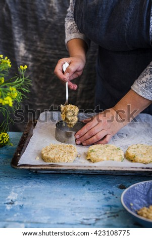 Veggies cutlets or patties recipe for burgers. Female making vegetable cutlets on a cooking sheet in summer day. Rustic dark blue styling. - stock photo