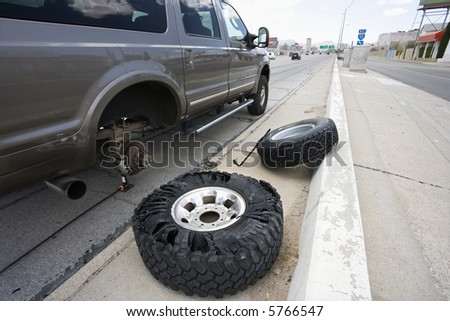 Vehicle brokendown along roadside with damaged tire needing replacement. - stock photo