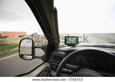 Vehicle dashboard with GPS and view through windshield of rainy highway ahead. - stock photo