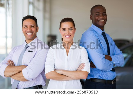 vehicle sales team with arms crossed inside car showroom - stock photo