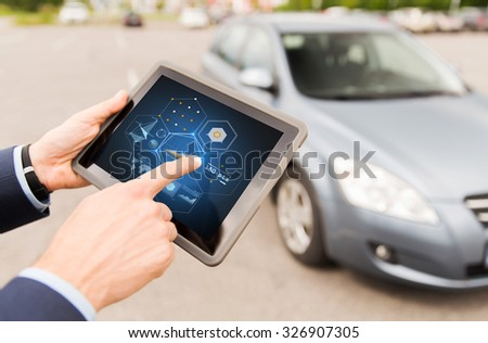vehicle, technology, diagnostics and people concept - close up of male hands with charts on tablet pc computer screen and car outdoors - stock photo
