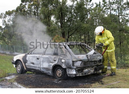 Vehicle that had been set on fire with fireman hosing out the flames. - stock photo