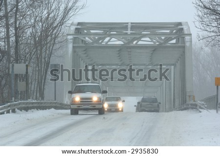 Vehicles crossing a bridge during a blizzard. - stock photo