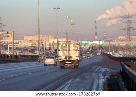 Vehicles riding on the dirty city highway at winter - stock photo