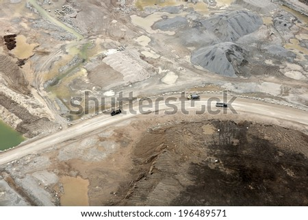 Vehicles using a dirt road surrounded by mainly dirt and water. - stock photo