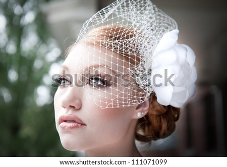 Veiled bride with red hair looks off into distance. - stock photo